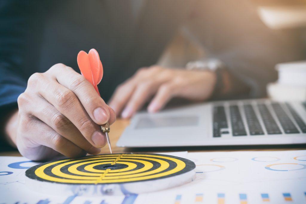 Man placing a dart inside of a bullseye, indicating he has met his goals